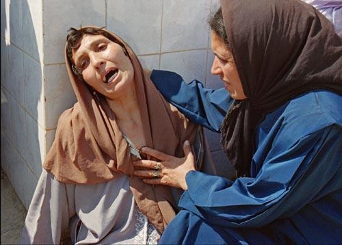 23 septembre 1997 - El Harrach, Algérie Une femme s'effondre de douleur devant l'hôpital de Zmirli après avoir appris qu'elle avait perdu plusieurs membres de sa famille à Bentalha dans un massacre attribué aux islamistes.